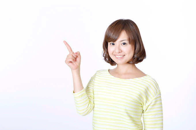 笑顔で指差しする女性